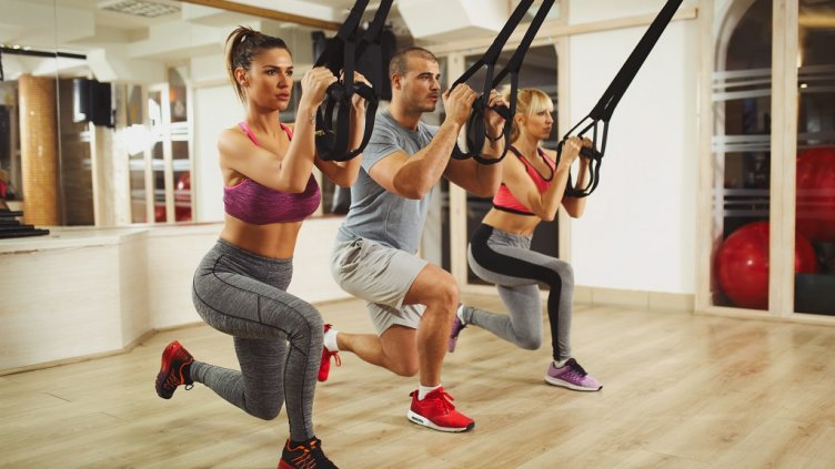 Three young athletic people are having TRX suspension training and doing arm and leg exercises at gym.