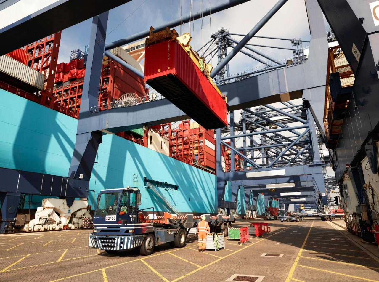 Crane lowering cargo container onto truck at Port of Felixstowe, England