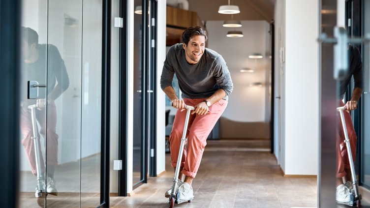 Happy young businessman enjoying while riding push scooter in office corridor